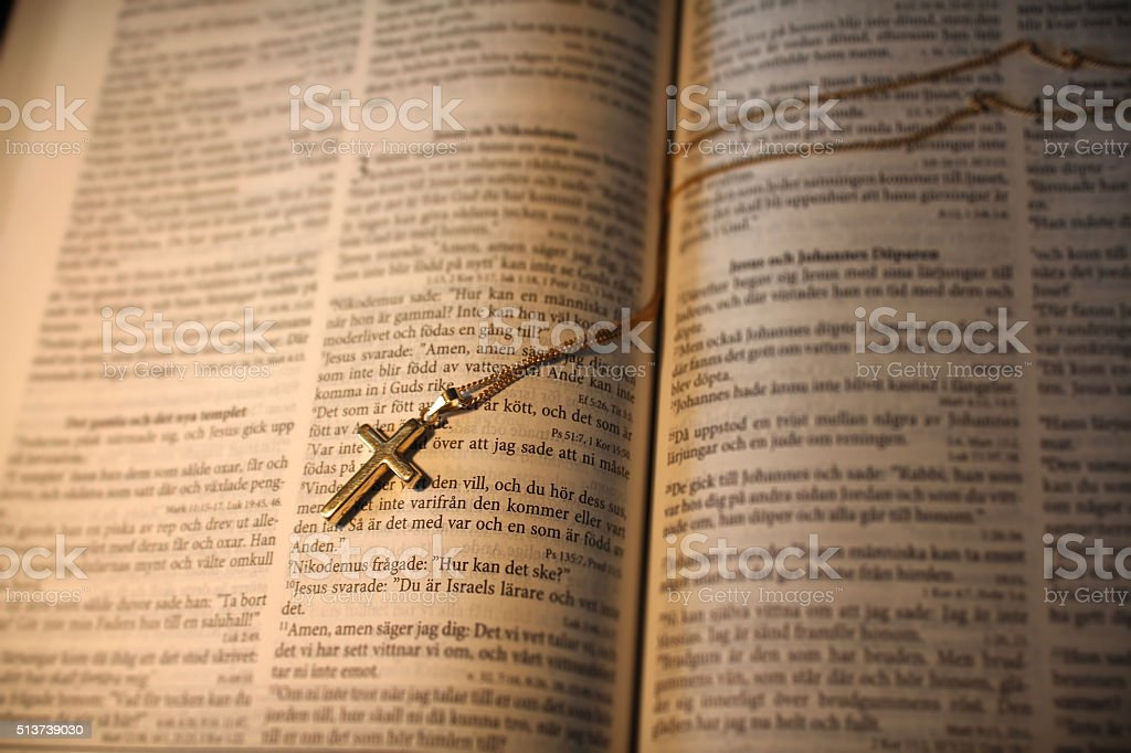 Genuine golden cross necklace on top of Sweish Bible stock photo