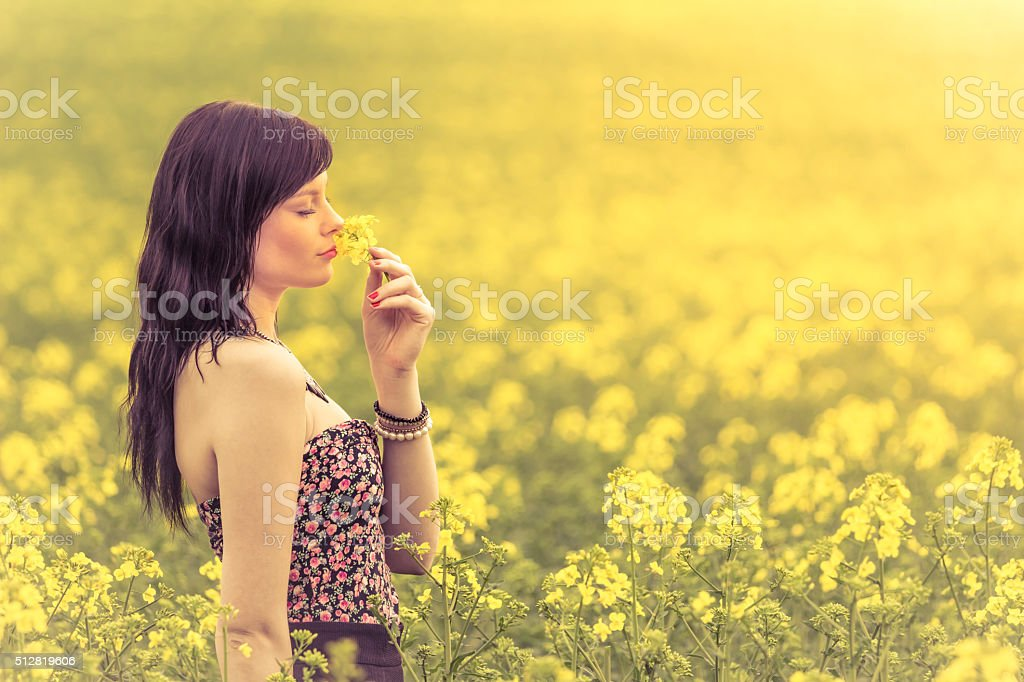 Genuine woman in meadow of yellow flowers sniffing flower stock photo