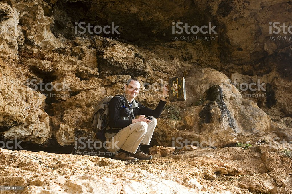 geocaching man with a box in his hand stock photo