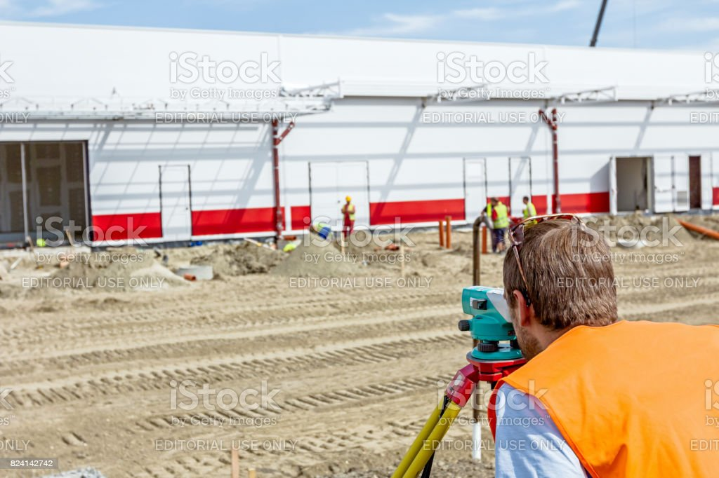 Geodesist is working with total station on a building site stock photo
