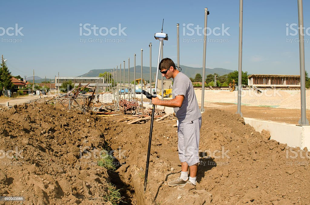 Geodesist measures at a countryside stadium stock photo