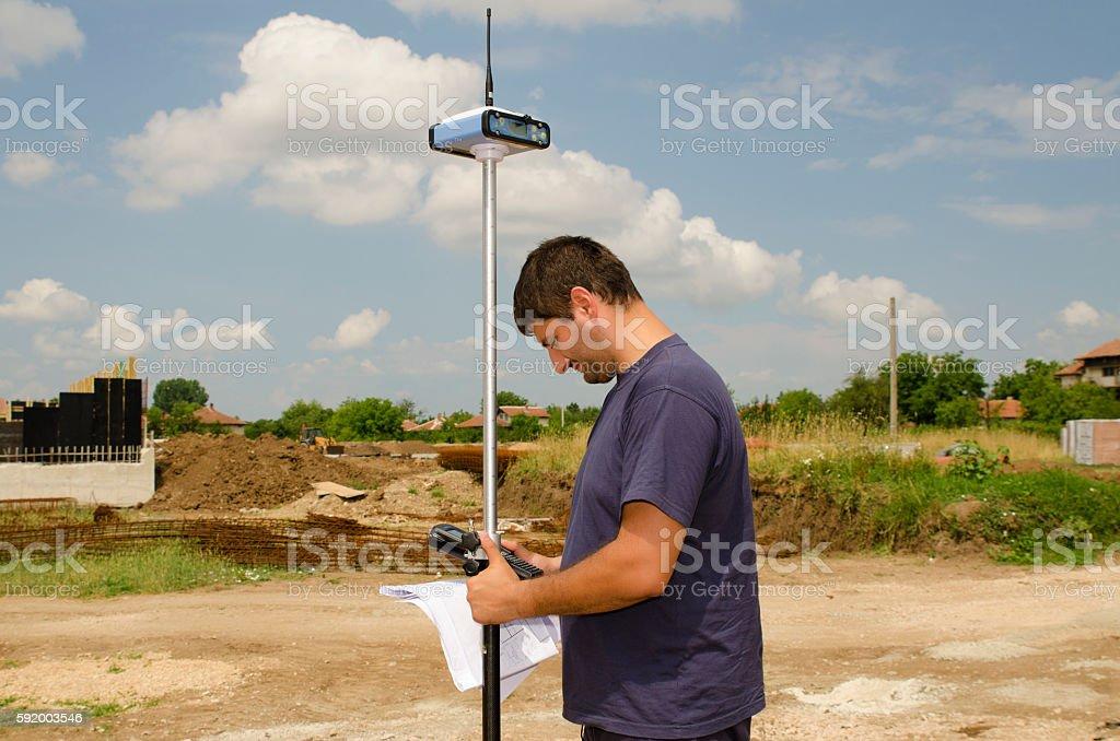 Geodesist working on a terrain stock photo