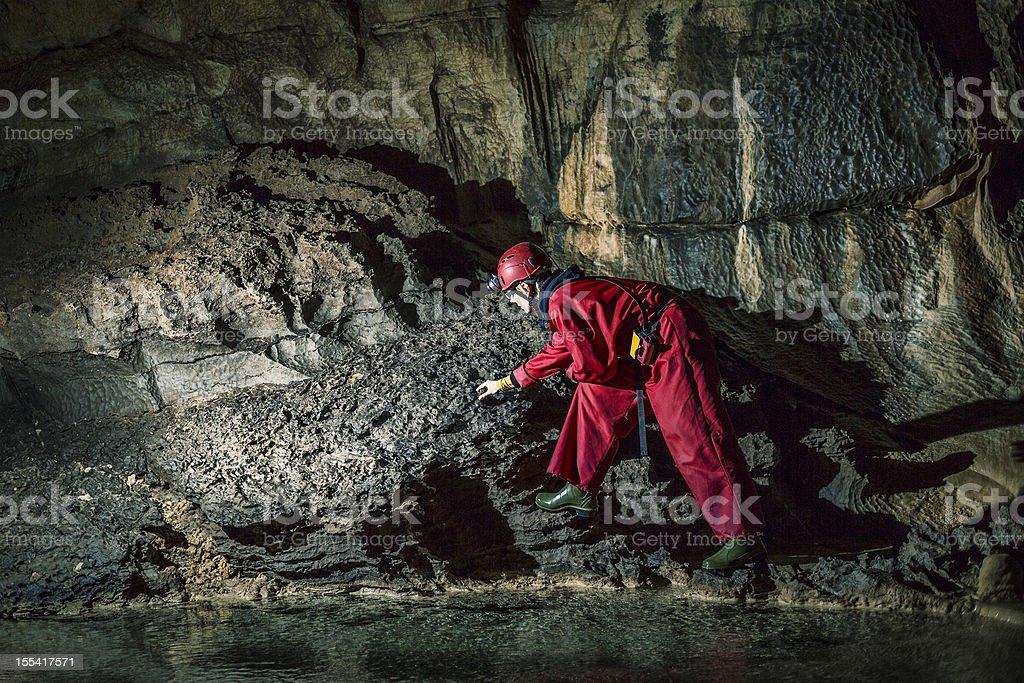 Geologist exploring caves deep underground stock photo
