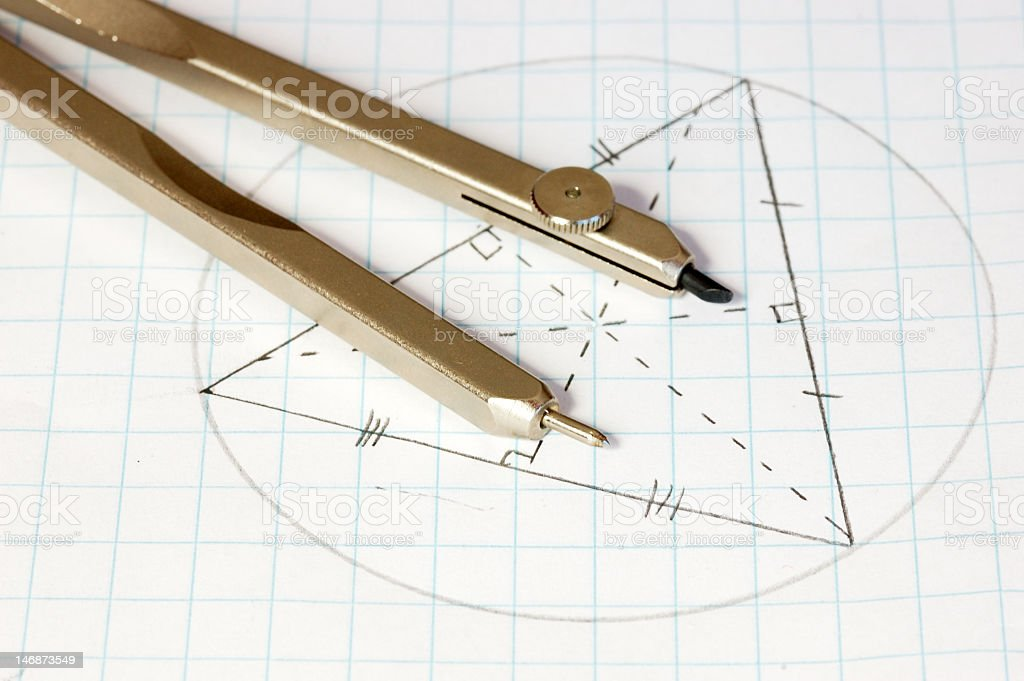Geometric symbol drawn on graph paper with a compass on top  royalty-free stock photo