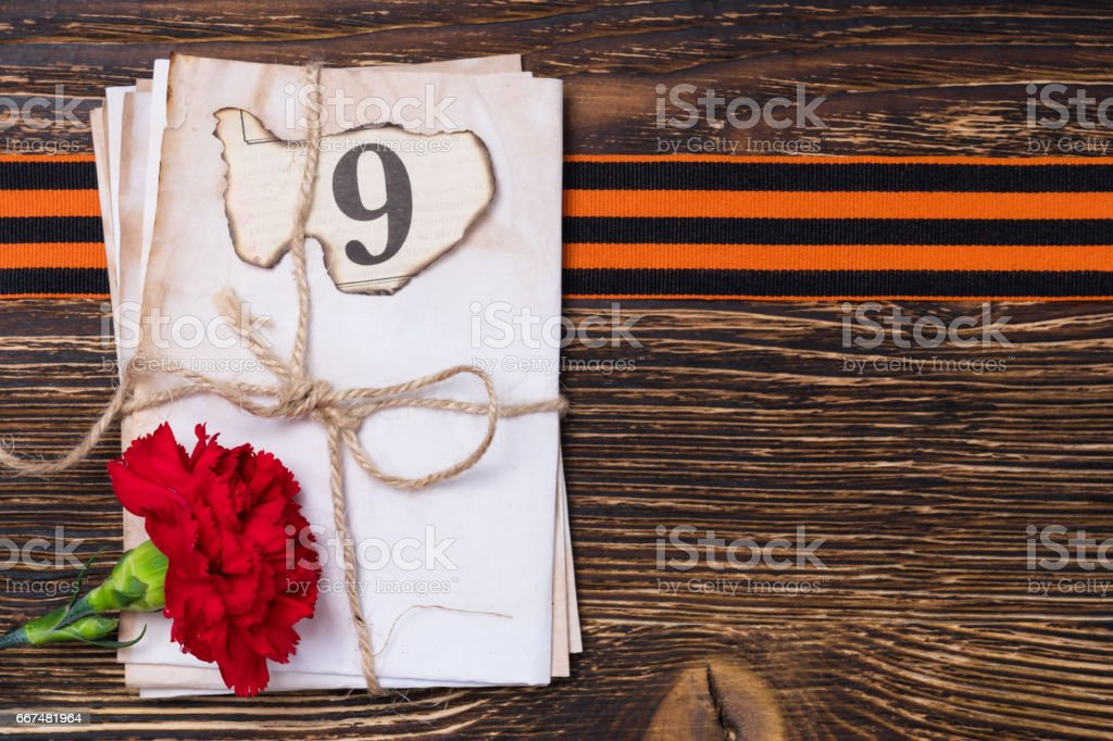George ribbon on the blackboard under letters and a red flower stock photo