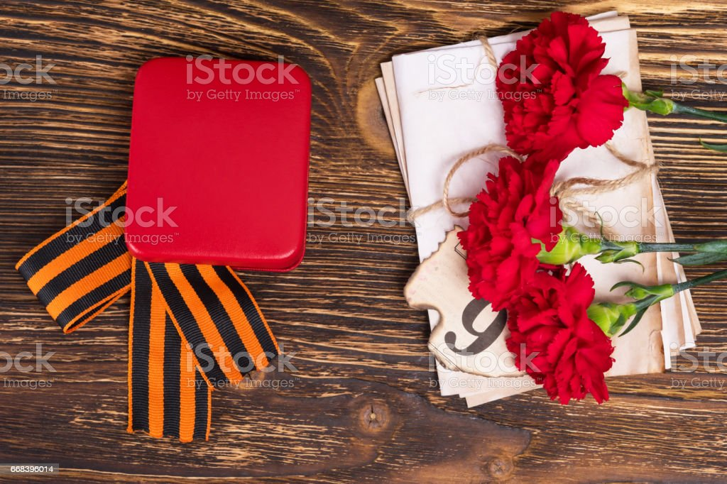 George's ribbon on the table with three carnations and letters stock photo