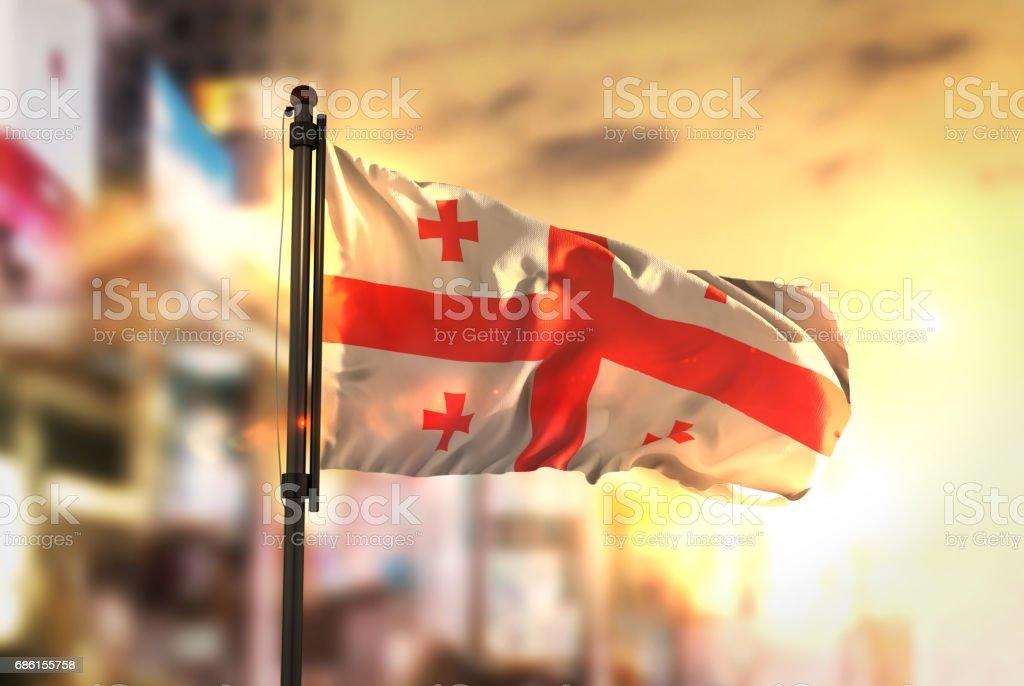 Georgia Flag Against City Blurred Background At Sunrise Backlight stock photo