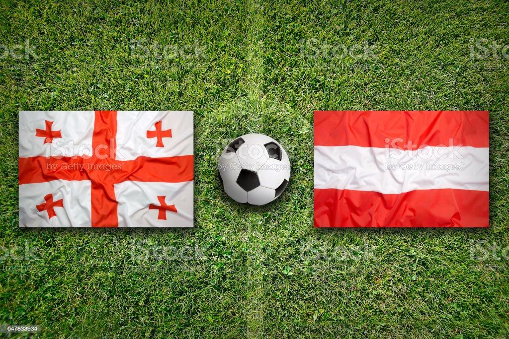 Georgia vs. Austria flags on soccer field stock photo