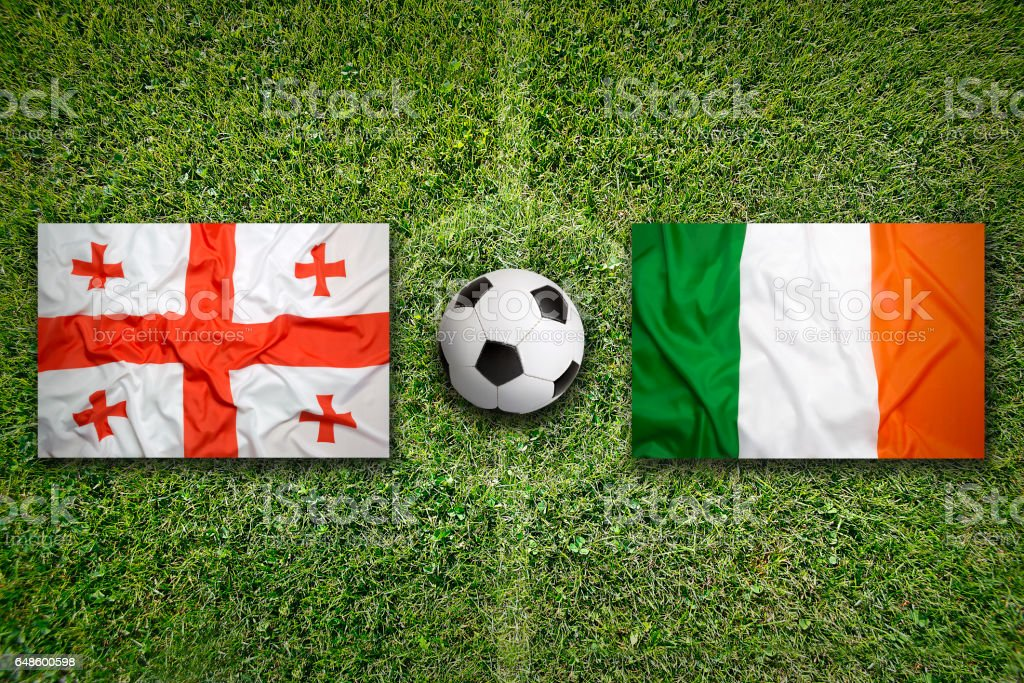 Georgia vs. Ireland flags on soccer field stock photo