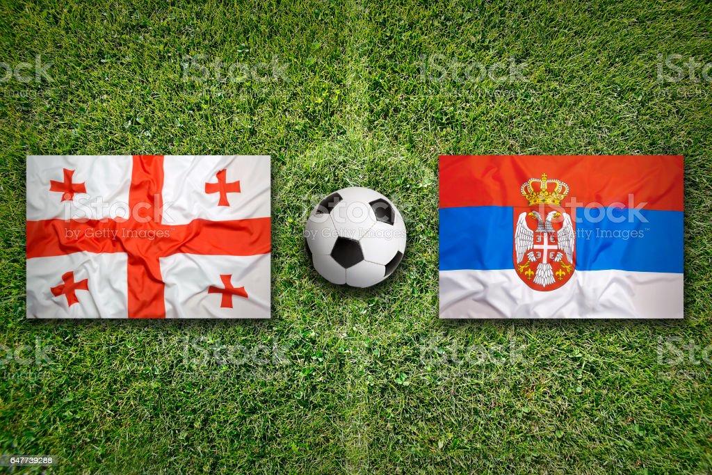 Georgia vs. Serbia flags on soccer field stock photo