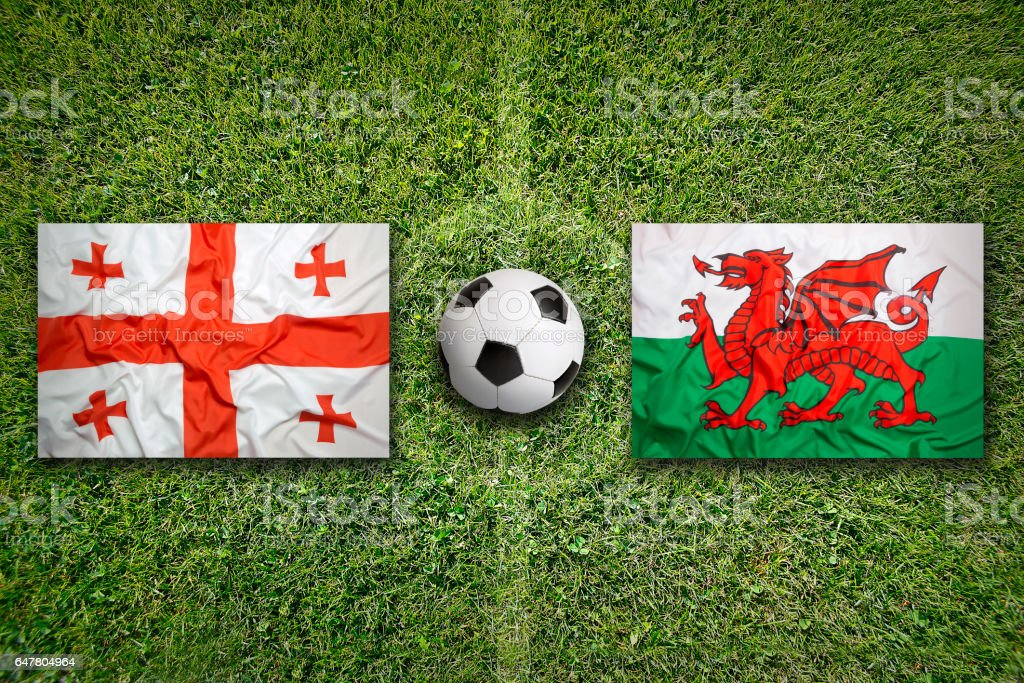 Georgia vs. Wales flags on soccer field stock photo