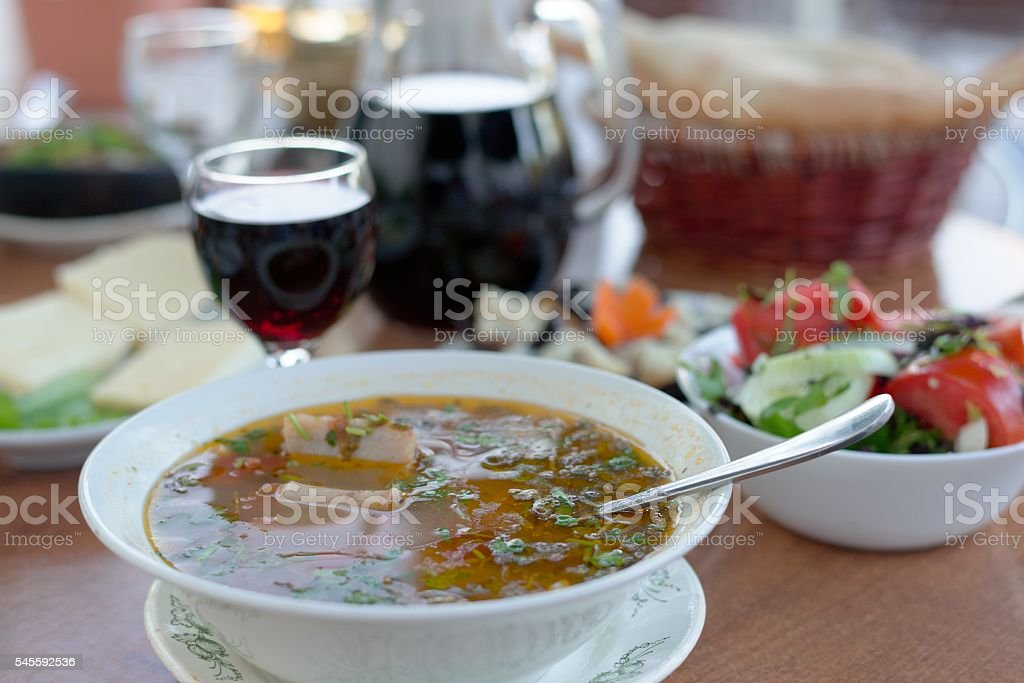 Georgian Beef-Walnut Spicy Soup with fresh herbs and rise stock photo