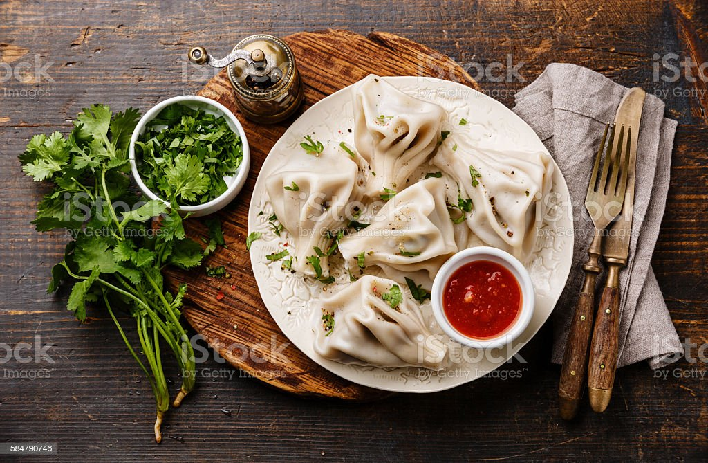 Georgian dumplings Khinkali with meat, greens and tomato sauce – Foto