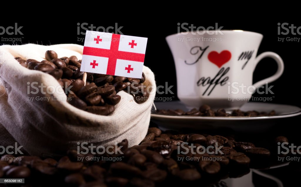 Georgian flag in a bag with coffee beans isolated on black background stock photo