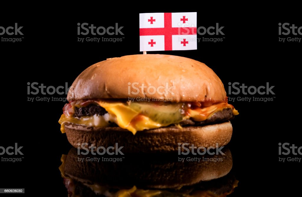 Georgian flag on top of hamburger isolated on black background stock photo