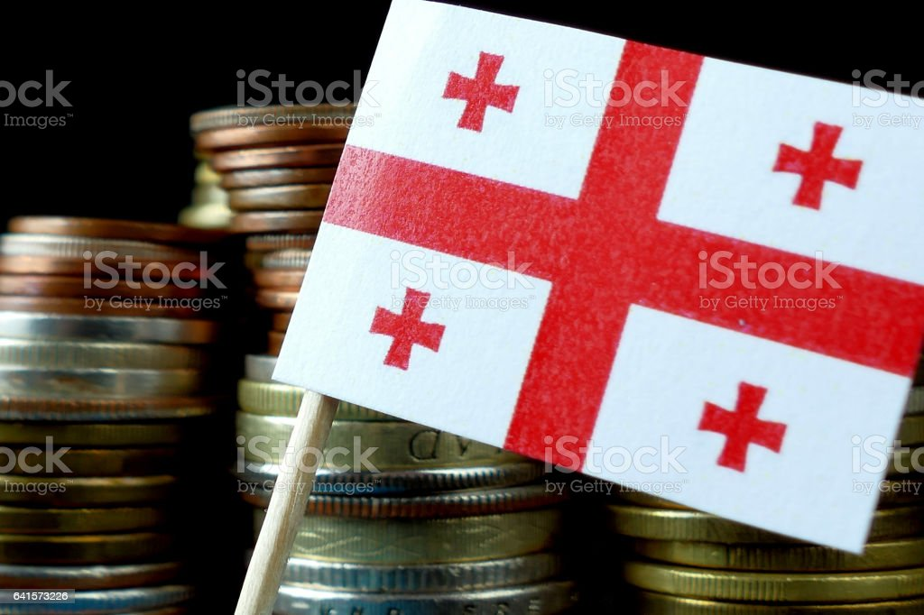 Georgian flag waving with stack of money coins macro stock photo