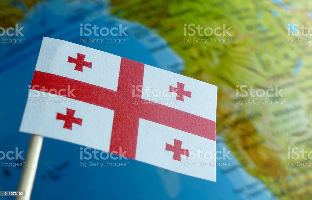 Georgian flag with a globe map as a background macro stock photo