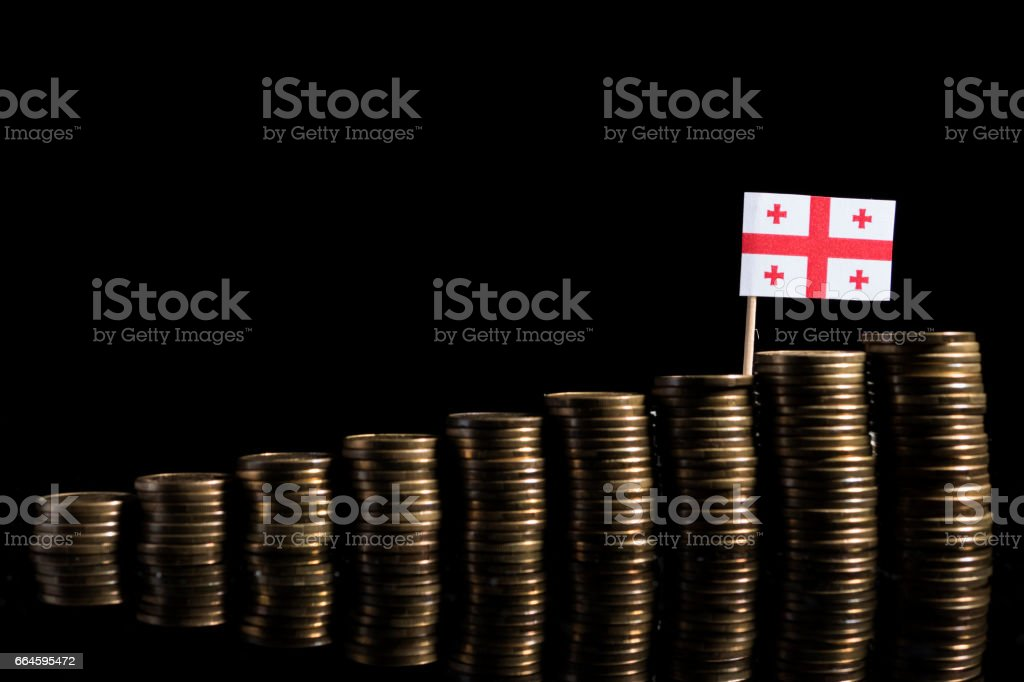 Georgian flag with lot of coins isolated on black background stock photo
