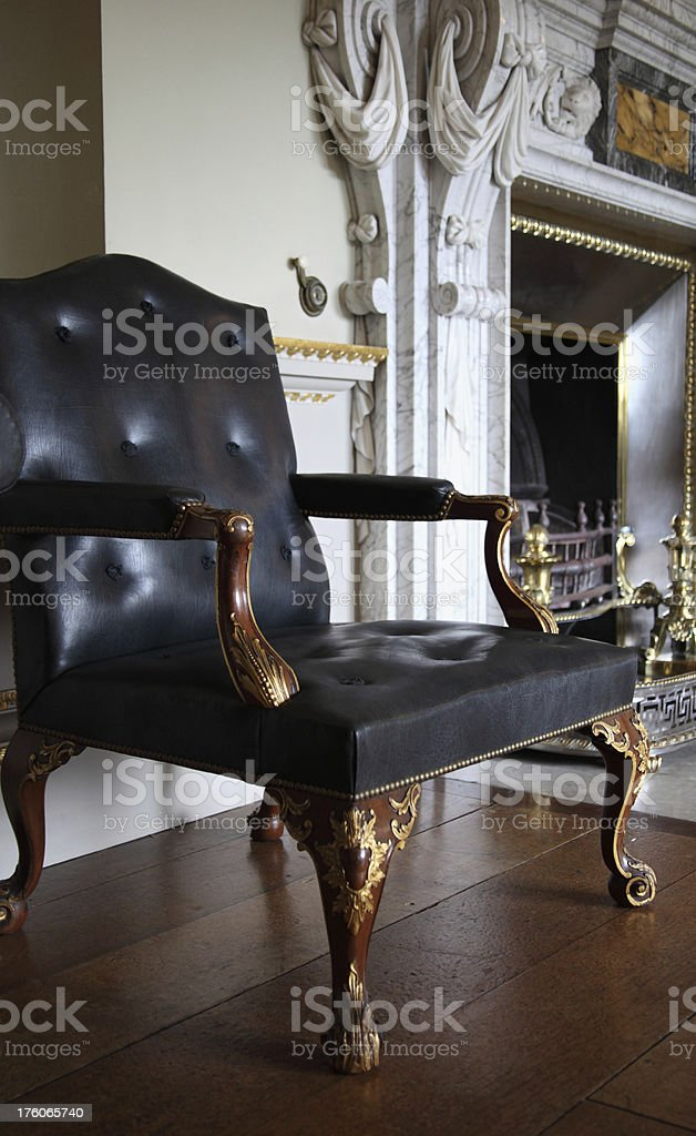 Georgian style leather chair by the fireplace stock photo