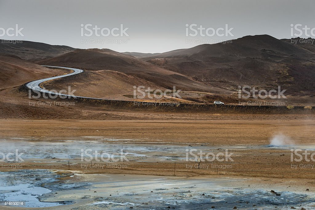 Geothermal mudpot Namafjall with curve road line and mountain background stock photo