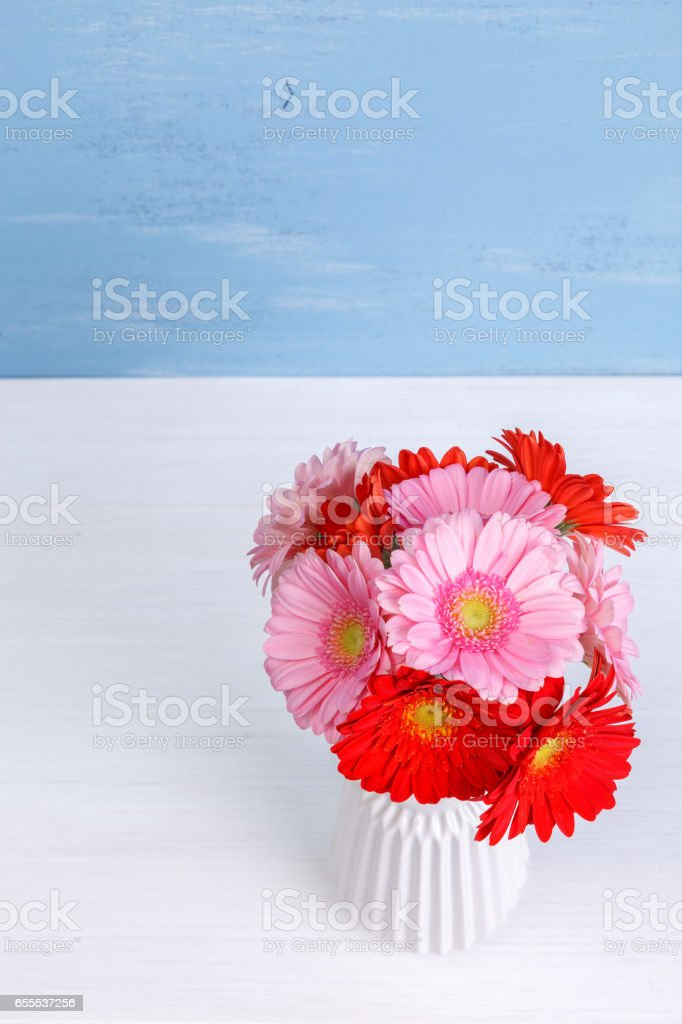 Gerbera flowers in vase on wooden background. stock photo