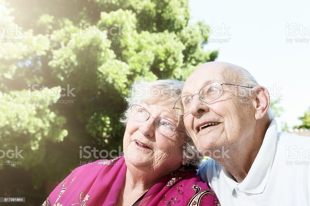 Geriatric couple in garden look up, smiling optimistically stock photo