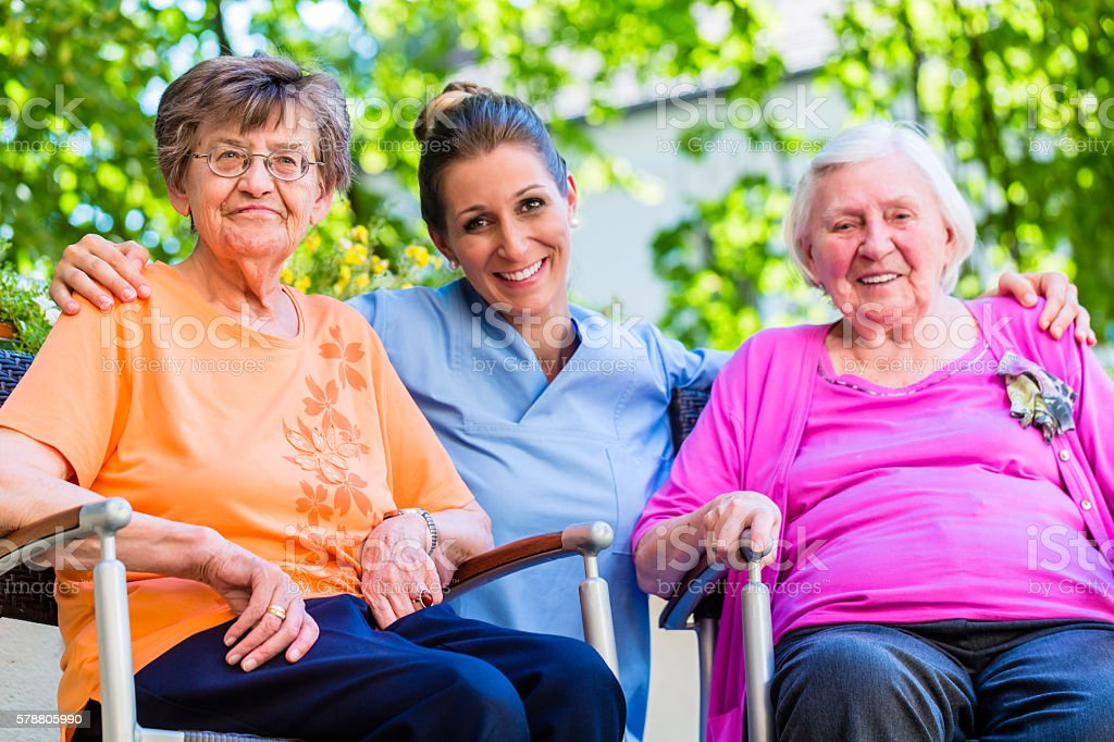 Geriatric nurse having chat with senior women stock photo