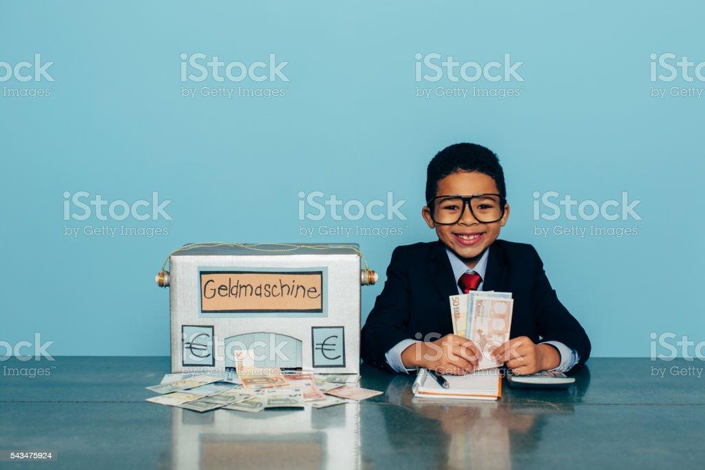 German Business Boy Makes Euros with Money Machine stock photo
