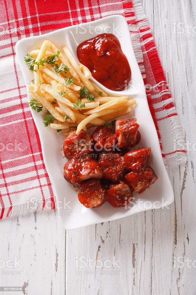 German cuisine: currywurst with french fries. Vertical top view stock photo