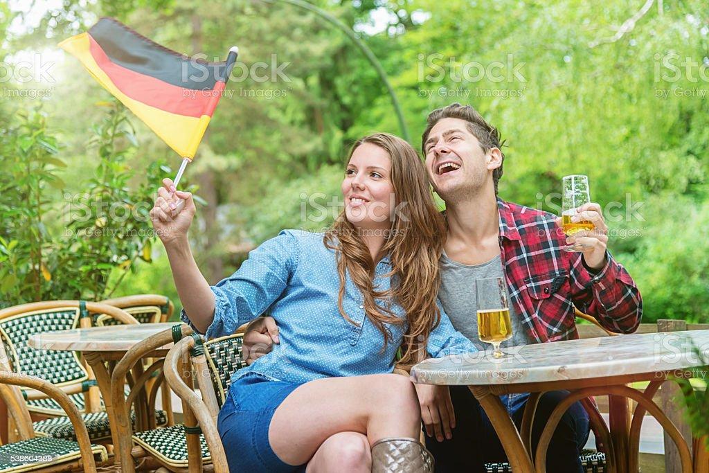German Fan Couple Fun Beer Garden Watching Soccer Game stock photo