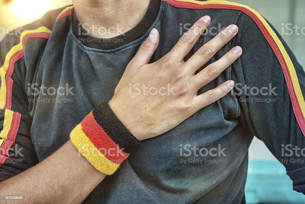 German Fan Putting Hand on Hearth During the National Anthem stock photo