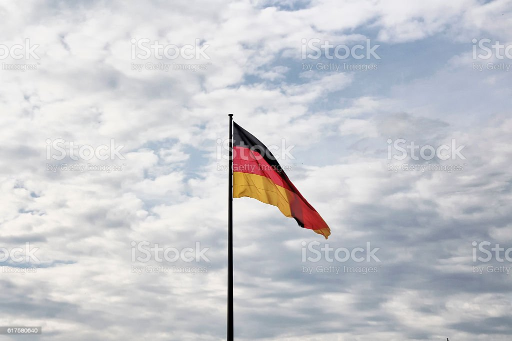 German flag waves with cloudy sky background stock photo