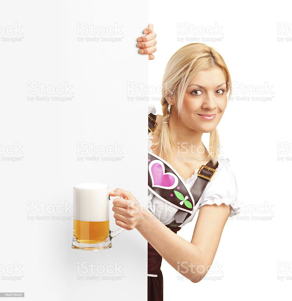 German girl holding a pint of beer behind billboard royalty-free stock photo