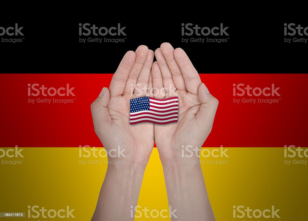 German Hands protecting the national flag of USA stock photo