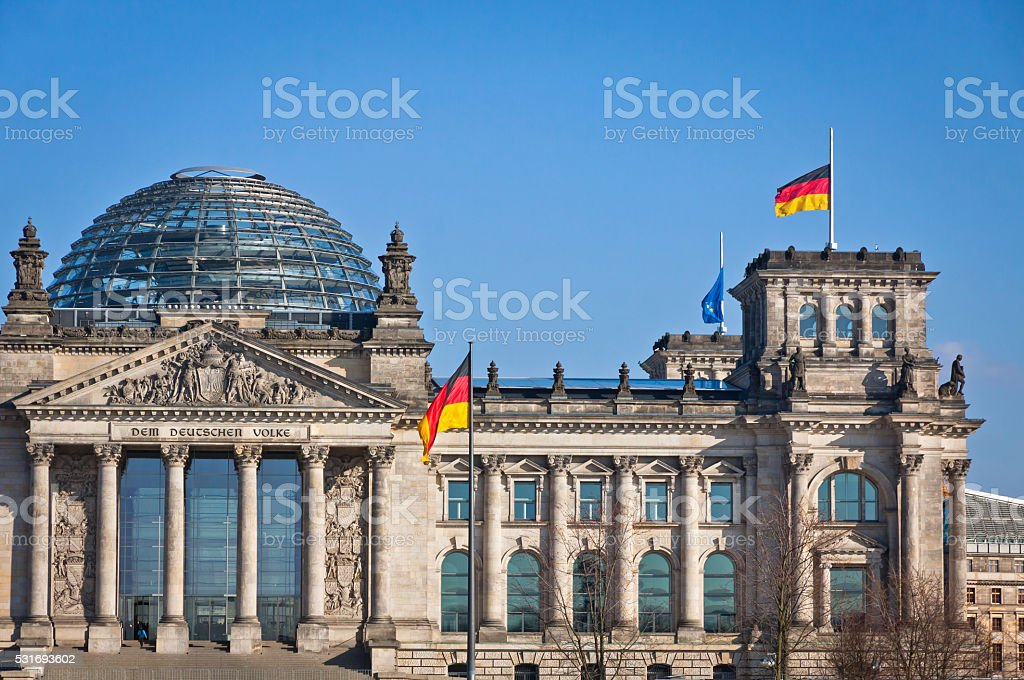 German National flags waving in front of German parliament buildi stock photo
