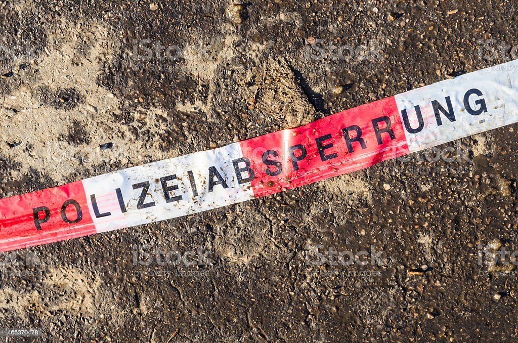 German police line red white tape on street asphalt dirt stock photo