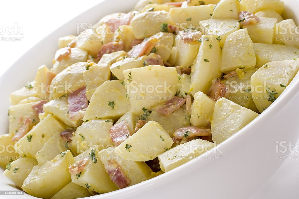 A German potato salad in a white bowl with seasoning stock photo