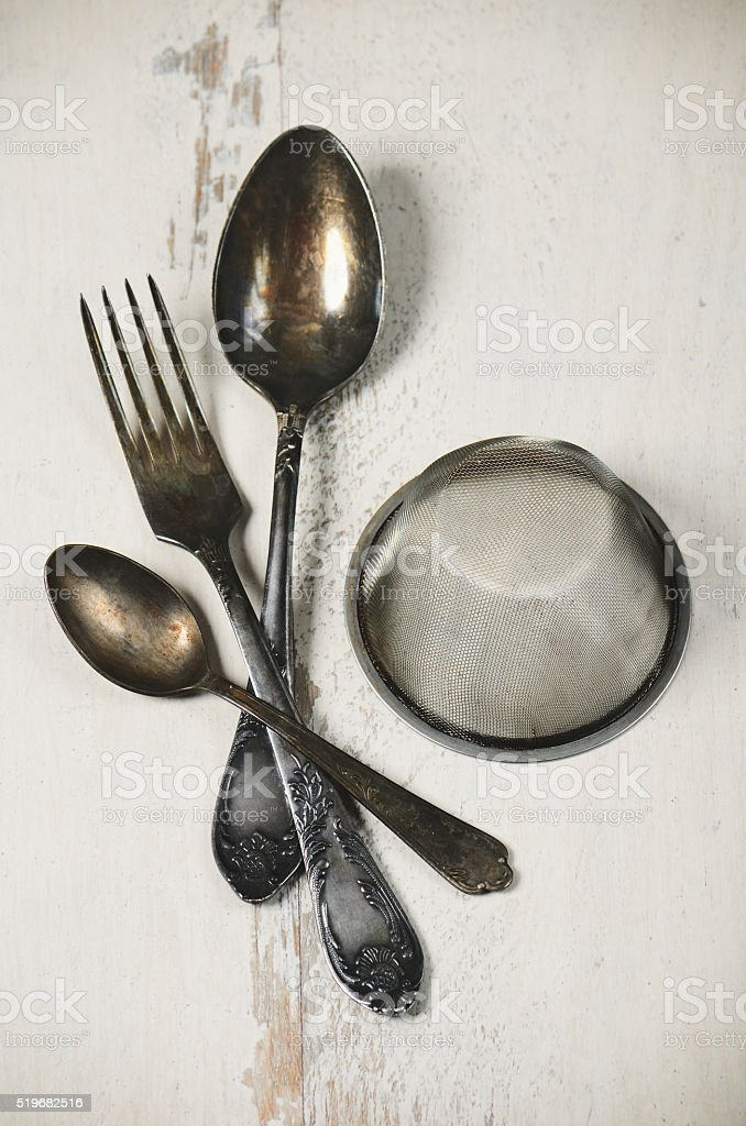 German silver spoon, fork and other utensils on  white wooden stock photo