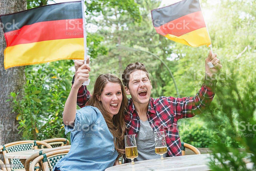 German Soccer Fan Couple Cheering in Beer Garden stock photo