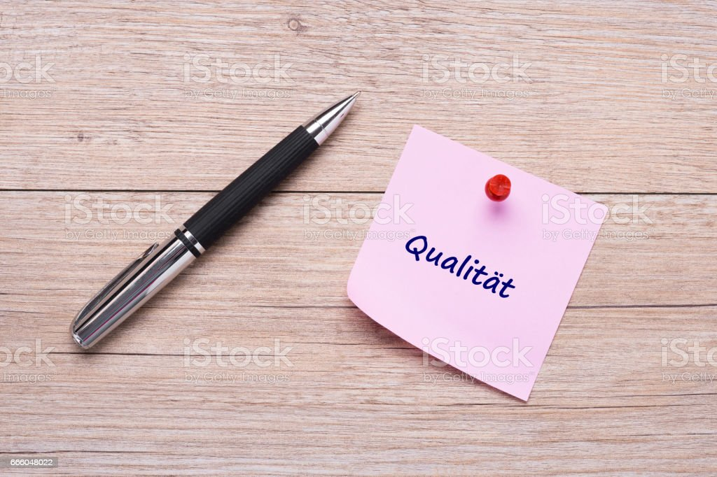 German word 'Qualität' as concept on pink sticky note with ballpoint pen stock photo