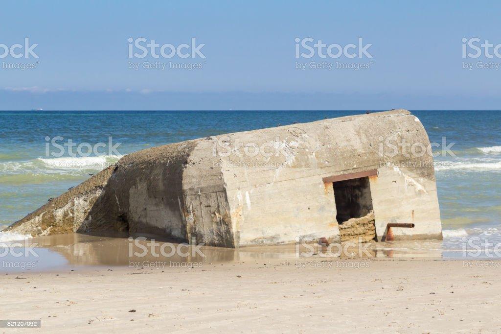 German World War II bunker half submerged, Skiveren beach, Denmark stock photo