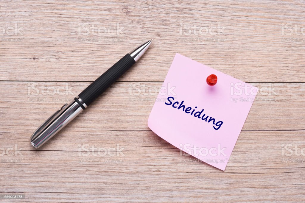 Germand word 'Scheidung' on pink sticky note with red pin as concept stock photo