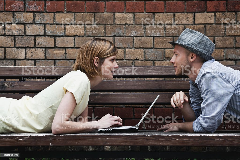 Germany, Berlin, Man and woman lying on bench and using laptop royalty-free stock photo
