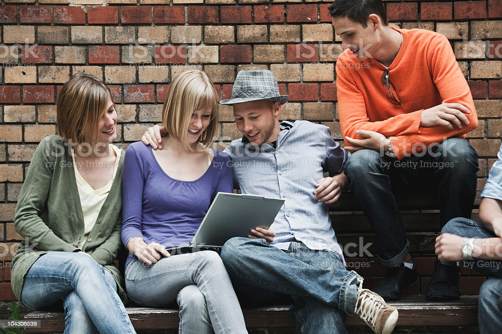 Germany, Berlin, Man and woman sitting with laptop on bench royalty-free stock photo