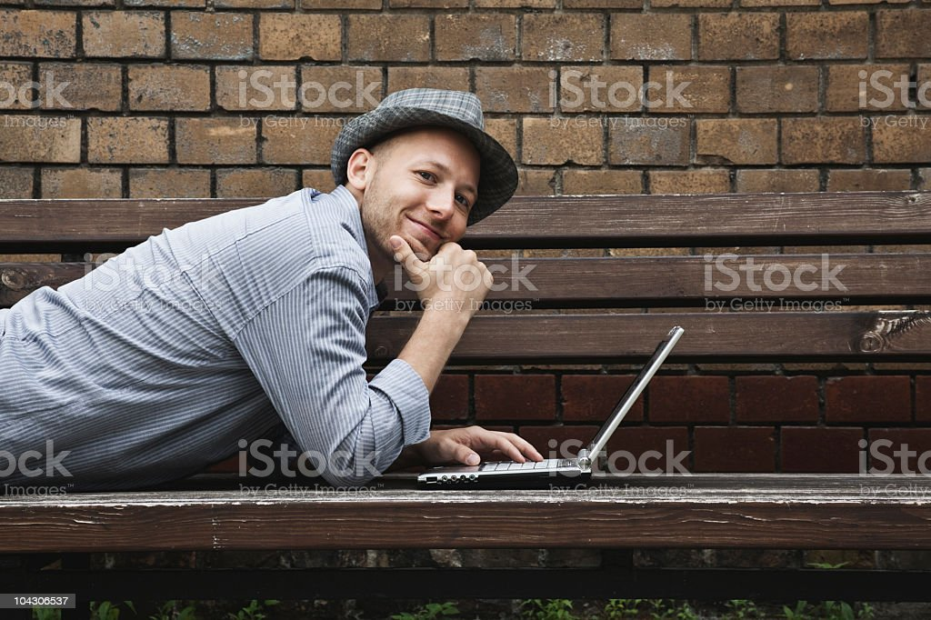 Germany, Berlin, Man lying and using laptop royalty-free stock photo