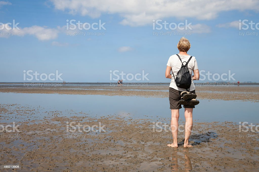 Germany, Lower Saxony, Low tide, woman standing on water's edge stock photo