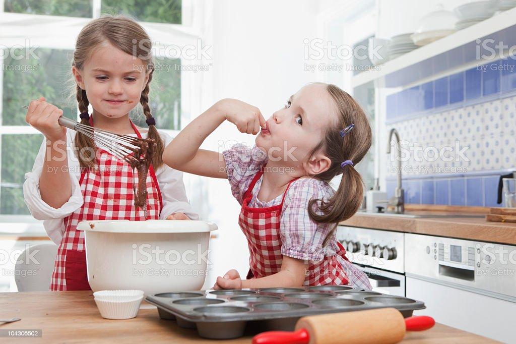 Germany, Munich, Girls (4-7) baking cookies and tasting royalty-free stock photo