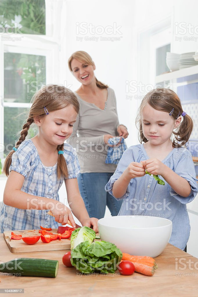Germany, Munich, Girls (4-7) chopping vegetables in kitchen, mother standing in background royalty-free stock photo