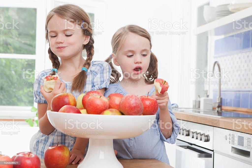 Germany, Munich, Girls (4-7) eating apple royalty-free stock photo