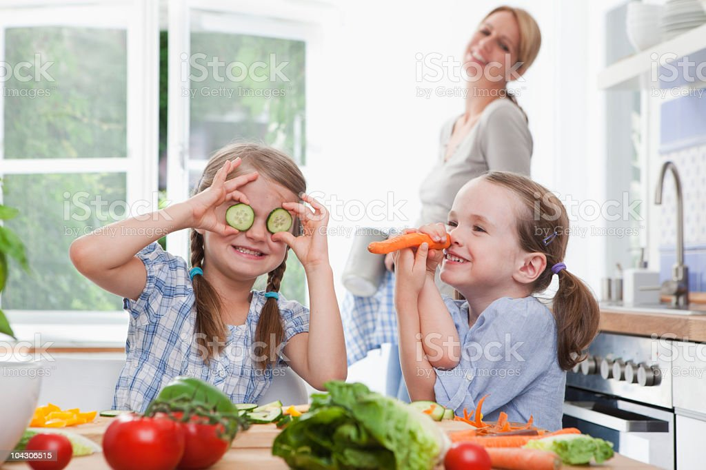 Germany, Munich, Girls (4-7) playing with vegetables in kitchen, mother standing in background royalty-free stock photo